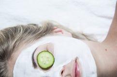 Young woman with clay facial mask in spa salon. Closeup portrait, half face Stock Photos