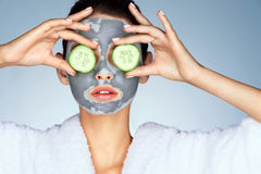 Young woman with a clay mask. Stock Photos