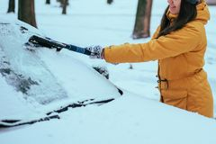 Young woman clean car after snow storm. With scraper royalty free stock photography