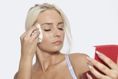 Young woman clean face with wet wipes and holding mirror Royalty Free Stock Image
