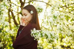Young woman with clean skin near a blooming apple tree. portrait of girl in spring park. stock photo