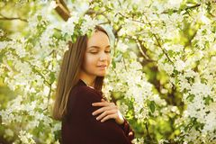 Young woman with clean skin near a blooming apple tree. portrait of girl in spring park. stock photos