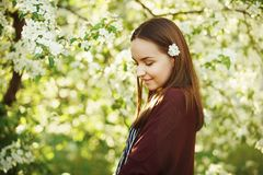 Young woman with clean skin near a blooming apple tree. portrait of girl in spring park. Spring shot of cute person royalty free stock image