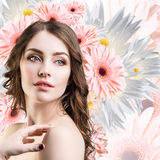 Young woman with clean skin over flowers. Royalty Free Stock Image