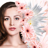 Young woman with clean skin over flowers. Stock Photography