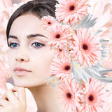 Young woman with clean skin over flowers. Stock Photos