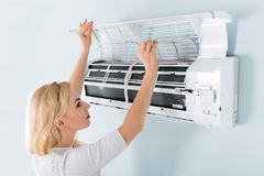 Woman Cleaning Air Conditioning System. A Young Woman Cleaning Air Conditioning System At Home Stock Images