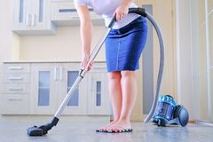 A young woman is cleaning the apartment. In the hands of a household appliance, vacuum cleaner. The concept of cleanliness and. Order in the premises royalty free stock photography