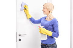 Young woman cleaning a door with cloth Stock Photos