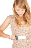 Young woman cleaning dust with lint roller Royalty Free Stock Photography