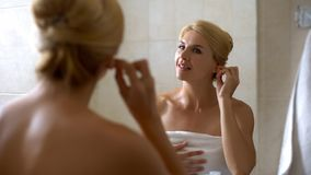 Young woman cleaning ears with cotton swab in bathroom, morning procedure health royalty free stock photography