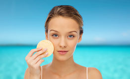 Young woman cleaning face with exfoliating sponge Stock Photos