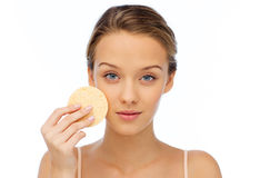 Young woman cleaning face with exfoliating sponge. Beauty, people and skincare concept - young woman cleaning face with exfoliating sponge Royalty Free Stock Images