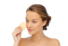 Young woman cleaning face with exfoliating sponge. Beauty, people and skincare concept - young woman cleaning face with exfoliating sponge Royalty Free Stock Image