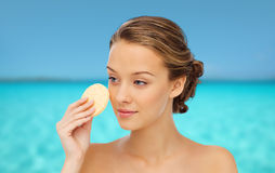 Young woman cleaning face with exfoliating sponge Stock Photo