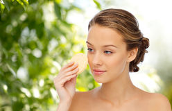 Young woman cleaning face with exfoliating sponge. Beauty, people and skincare concept - young woman cleaning face with exfoliating sponge over green natural Stock Photo