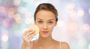 Young woman cleaning face with exfoliating sponge. Beauty, people and skincare concept - young woman cleaning face with exfoliating sponge over purple holidays Royalty Free Stock Photos