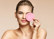 Young woman cleaning face with exfoliating sponge. Portrait of beautiful woman on beige background. Youth and skin care concept Royalty Free Stock Photo