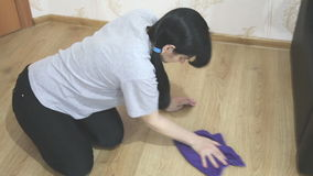 Young woman cleaning the floor with a cloth stock video