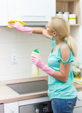 Young woman cleaning furniture in the kitchen Stock Image