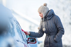 Young woman cleaning her car from snow and frost Royalty Free Stock Image