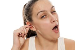 Woman cleaning her ears. Young woman cleaning her ears with a cotton swab Royalty Free Stock Photography