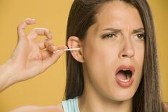 Young Woman Cleaning Her Ears With Cotton Sticks Stock Photos