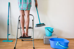 Young woman cleaning home with ladder and brush Stock Photos