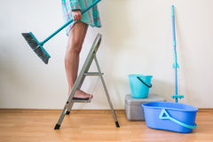 Young woman cleaning home with ladder and brush Stock Image