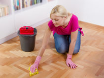 Young Woman Cleaning Home. Young woman cleaning and mopping floor at home Stock Photography