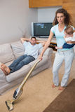 Young woman cleaning house while carrying baby Royalty Free Stock Photography