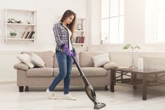 Young woman cleaning house with vacuum cleaner stock images