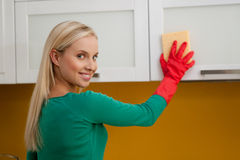 Young woman cleaning kitchen. Beautiful young woman cleaning kitchen Stock Photo