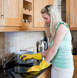 Young woman cleaning a kitchen Royalty Free Stock Photography