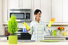 Young woman cleaning kitchen. Smiling young black woman with sponge and rubber gloves cleaning kitchen stock photography