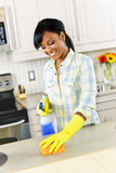 Young woman cleaning kitchen. Smiling young black woman with sponge and rubber gloves cleaning kitchen royalty free stock images