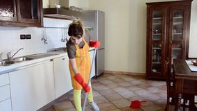 Young woman cleaning the kitchen floor stock video footage