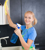 Young woman cleaning kitchen Stock Images