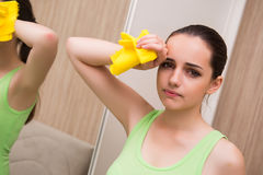The young woman cleaning mirror at home Stock Photography