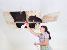 Young Woman cleaning mold on ceiling.Ceiling panels damaged huge. Hole in roof from rainwater leakage.Water damaged ceiling royalty free stock images