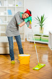 Young woman cleaning and mopping floor at home. Stock Images