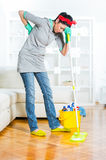 Young woman cleaning and mopping floor at home. Royalty Free Stock Image