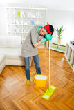 Young woman cleaning and mopping floor at home. Stock Photos