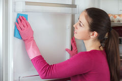 Young woman cleaning refrigerator with rag at home Royalty Free Stock Photography
