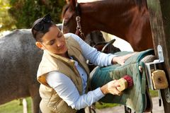 Young woman cleaning saddlery Royalty Free Stock Photos