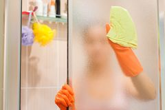 Young woman cleaning a shower door, dusting stock photo