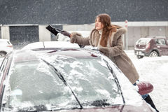 Young woman cleaning snow from car roof using brush Stock Photos
