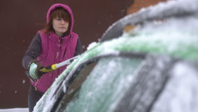 Young woman cleaning Snow and Ice off her Car. Winter snow storm stock footage