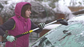 Young woman cleaning Snow and Ice off her Car. Winter snow storm stock video