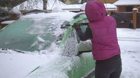 Young woman cleaning Snow and Ice off her Car. Winter snow storm stock video footage